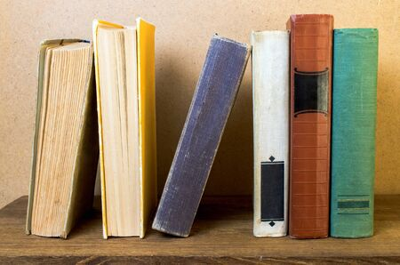 old books stacked on a wooden shelf Archivio Fotografico