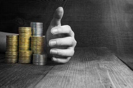 hand picks up piles of money, black and white toning