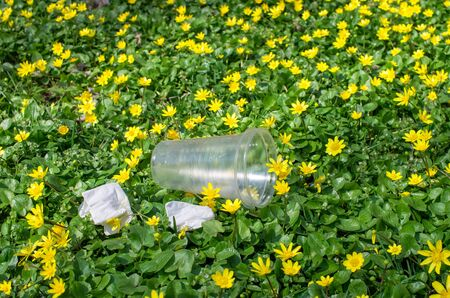 discarded plastic cups and napkins in the grass of the park