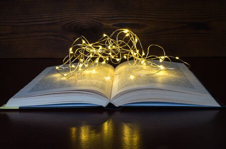 open book light of a garland in the dark wooden background