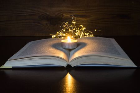 burning candle on an open book in the dark