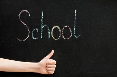 chalk inscription on blackboard - school, hand and thumb up