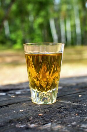 glass of whiskey on a table in a forest