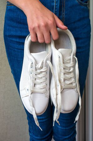 new white sneakers in the hands of the girl