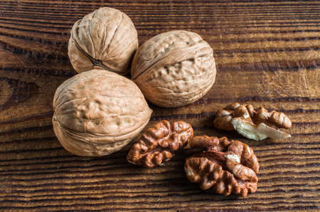 whole and open walnuts, walnut grain, on a wooden table 免版税图像