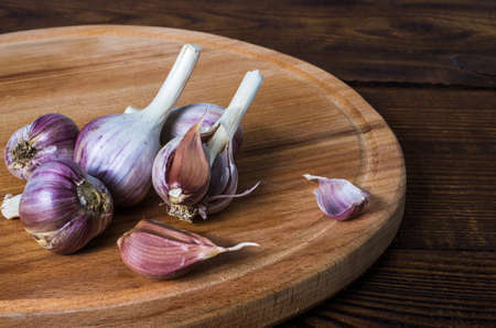 heads of garlic on a cutting board made of wood, round shape. Rustic style