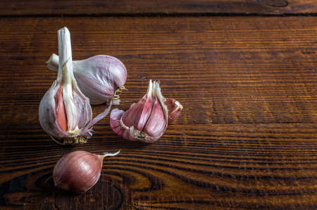 heads of garlic on a wood board. Rustic style 免版税图像