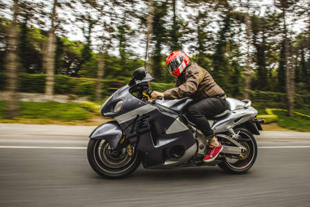High speed motorcycle biking on the road accross the forest Archivio Fotografico