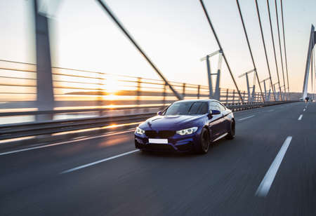 Business class black sedan driving on the bridge