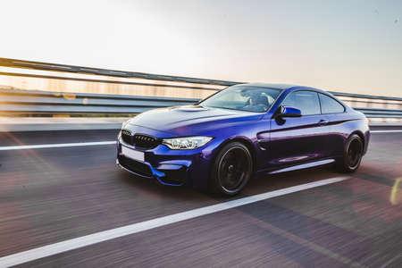 Blue sedan speed drive on the highway