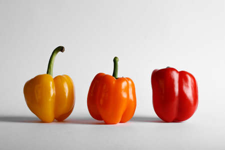Tricolor peppers standing on white backdrop