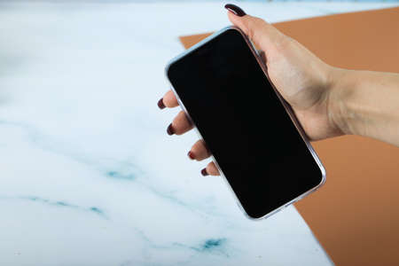 Black smartphone in the hand of a woman isolated on blue