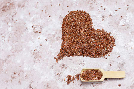 Heart shaped flax seeds on concrete background with space for copy,top view Foto de archivo