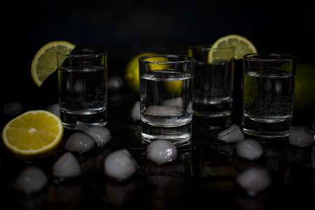 Alcohol shots with lime and ice cubes on black background