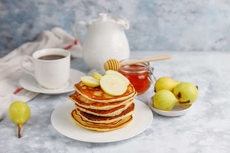 Homemade breakfast: american style pancakes served with pears and honey with a cup of tea on concrete background. Top view and copy space