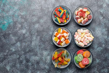 Colorful candies, jelly and marmalade on dark grey background,top view