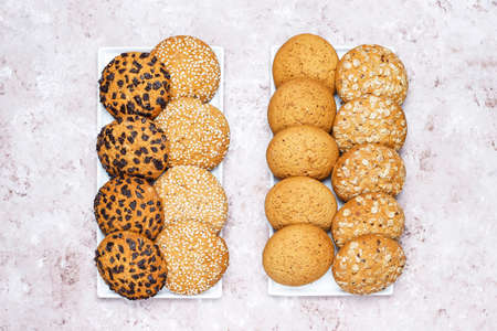 Set of various american style cookies on a light concrete background. Shortbread with confetti, sesame seed, peanut butter, oatmeal and chocolate chip cookies. Stock Photo