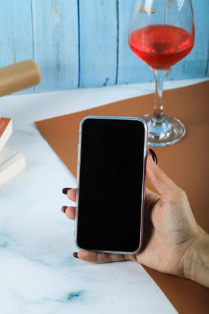 Taking a black smartphone in the hand around a glass of wine Banque d'images