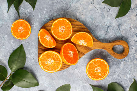 Citrus background with fresh sliced oranges on cutting board on concrete background,top view
