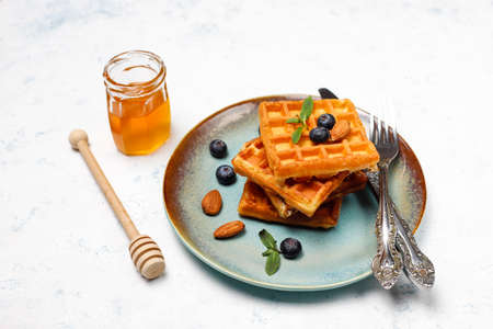 Traditional belgian waffles with fresh berries and honey on grey concrete background. Flat lay, top view, copy space.