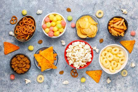 Collations salées. Bretzels, chips, craquelins, pop-corn dans des bols. Produits malsains. nourriture mauvaise pour la silhouette, la peau, le cœur et les dents. Assortiment d'aliments à base de glucides rapides