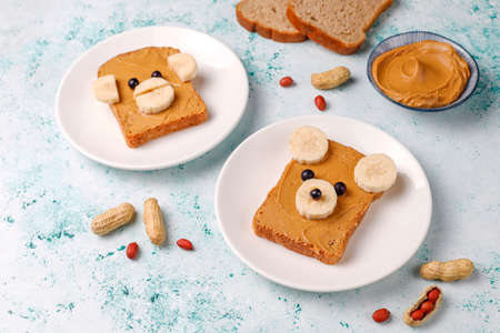 Funny bear and monkey face sandwich with peanut butter, banana and black currant on light background,top view