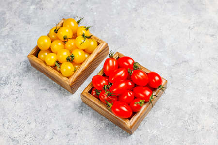 Arrangement of colorful fresh assorted tomatoes on light concrete background,top view 免版税图像
