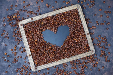 Composition with roasted coffee beans and coffe bean shaped cookies on dark brown background