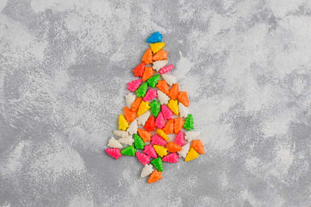 christmas tree shaped sparkle candies on a gray table. Top view, flat lay Stock Photo