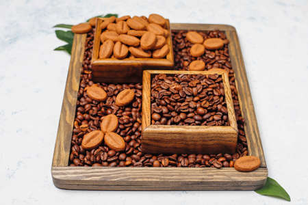 Composition with roasted coffee beans and coffe bean shaped cookies on light background