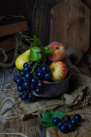 Autumn fruits on rustic background,dark photo