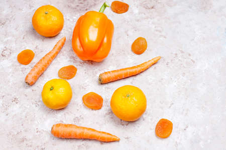 Fresh orange foods on light concrete background,top view