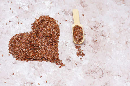 Heart shaped flax seeds on concrete background with space for copy,top view Stock fotó