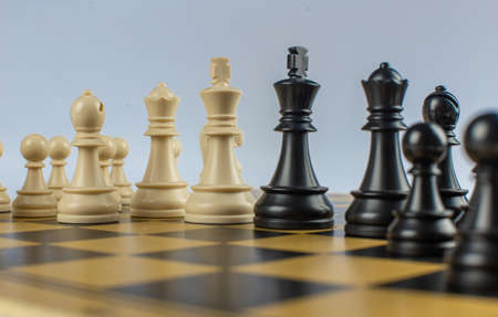 White and black figures on a chessboard on isolated white background