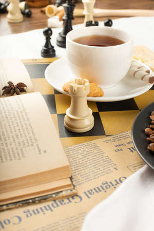 A book,a cup of tea and a chess rook