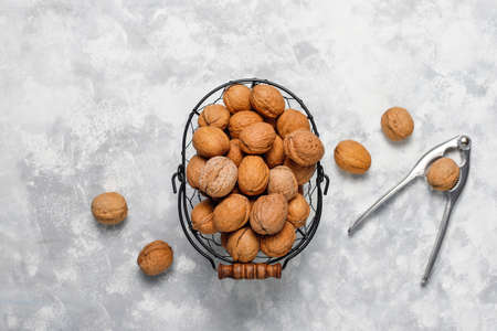 Whole walnuts in shell in food metal basket, walnut kernels. Top view on concrete background