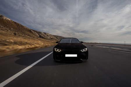 Black velvet sport sedan on the road. Front view