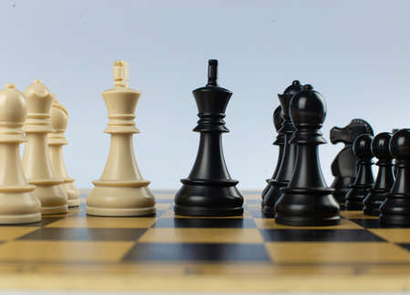 White and black figures on a chessboard on isolated white background Imagens