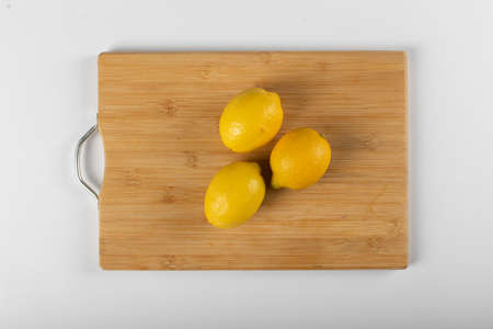 Three lemons on a wooden board isolated on white