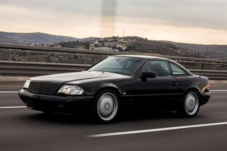 Black sedan car high speed drive on the highway