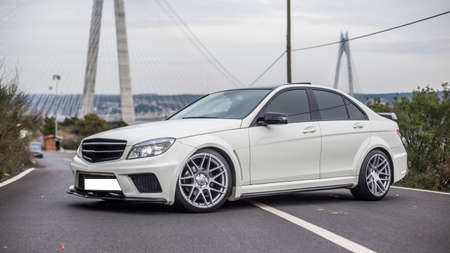 White business class sedan parking in the middle of the road