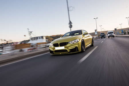 Golden sport sedan car on the autobahn. high speed drive, angle view