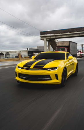 Yellow sport car with black stripes on it