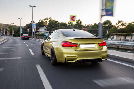 Golden color luxury sport sedan on the road 免版税图像