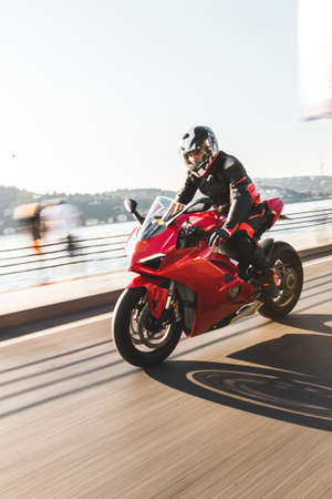 A biker in gear and helmet biking a red motorcycle in the port