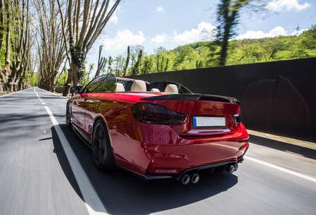 Red cabriolet parked in a green area Zdjęcie Seryjne