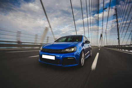 Blue hatchback car in parking mode in the bridge in a cloudy weather