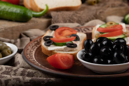 Sandwiches with tomato and black olives.