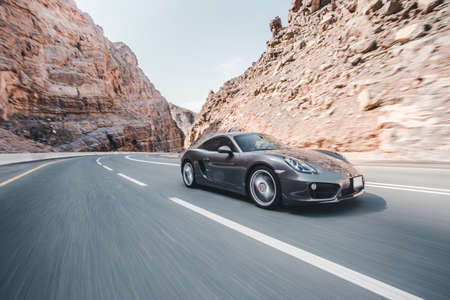 Driving a grey color sport car through the hills