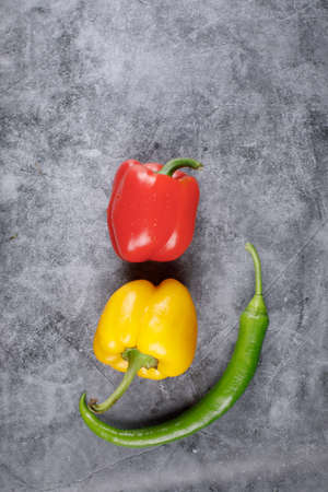 Artistic photo shooting of red, yellow bell pepper and a green chili. Top view.